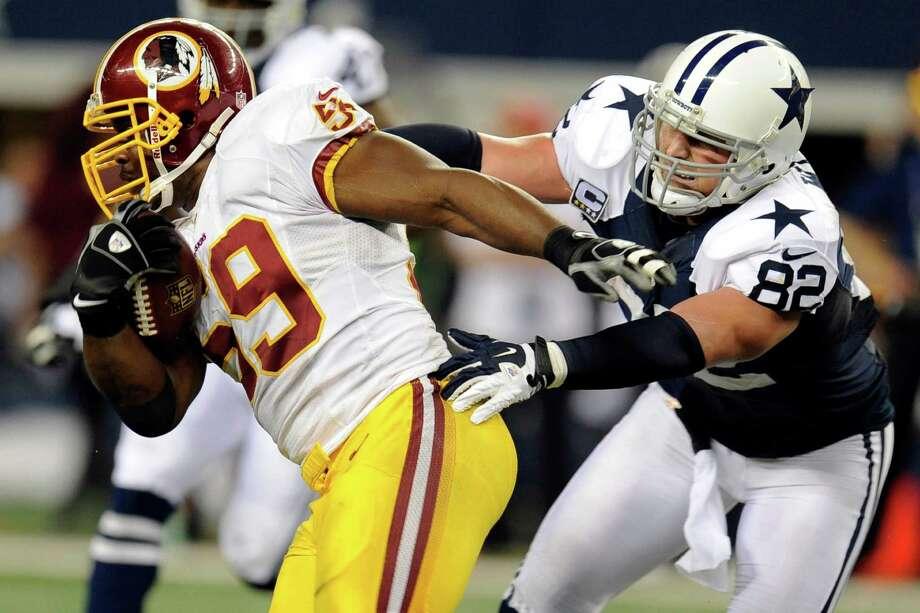 Washington Redskins inside linebacker London Fletcher (59) escapes a tackle by Dallas Cowboys' Jason Witten (82) after making an interception in the second half of an NFL football game, Thursday, Nov. 22, 2012, in Arlington, Texas. (AP Photo/Matt Strasen) Photo: Matt Strasen, Associated Press / FR170476 AP
