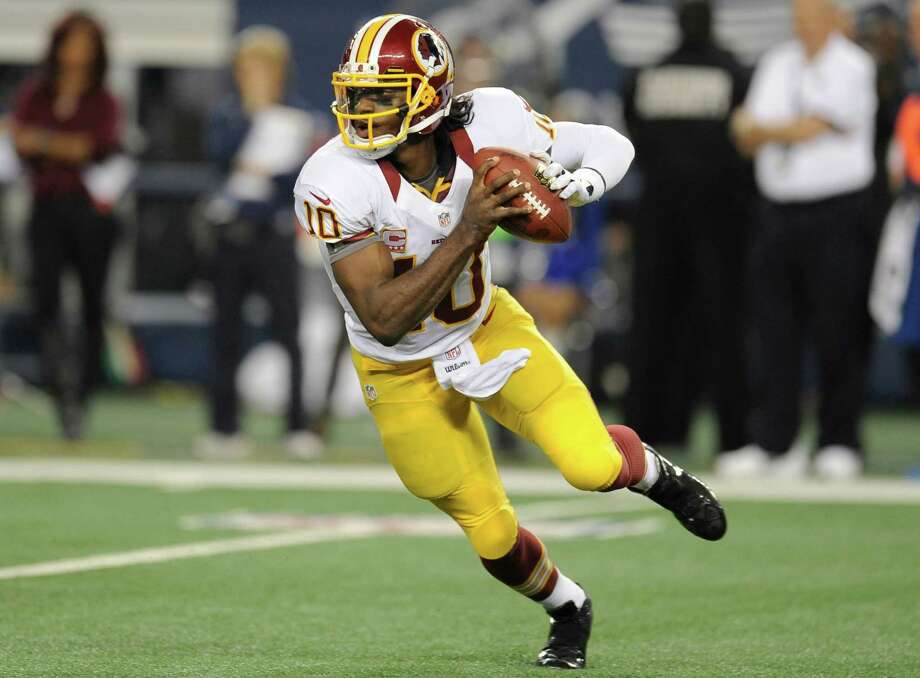 Washington Redskins quarterback Robert Griffin III (10) scrambles out of the pocket in the second half of an NFL football game against the Dallas Cowboys Thursday, Nov. 22, 2012 in Arlington, Texas. (AP Photo/Matt Strasen) Photo: Matt Strasen, Associated Press / FR170476 AP