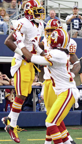 Washington Redskins' Aldrick Robinson (from left), celebrates with teammates Brandon Banks and Leonard Hankerson after scoring a touchdown against the Dallas Cowboys during first half action Thursday Nov. 22, 2012 at Cowboys Stadium in Arlington, Tx. Photo: Edward A. Ornelas, Express-News / © 2012 San Antonio Express-News