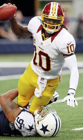 Washington Redskins' Robert Griffin III is sacked by Dallas Cowboys' Jason Hatcher during first half action Thursday Nov. 22, 2012 at Cowboys Stadium in Arlington, Tx. Photo: Edward A. Ornelas, Express-News / © 2012 San Antonio Express-News