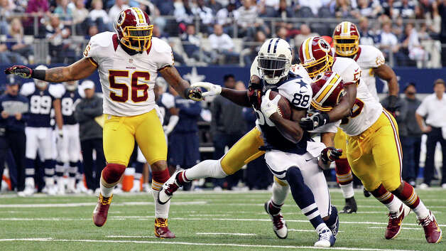 Dallas Cowboys' Dez Bryant is tackled by Washington Redskins defenders during first half action Thursday Nov. 22, 2012 at Cowboys Stadium in Arlington, Tx. Photo: Edward A. Ornelas, Express-News / © 2012 San Antonio Express-News