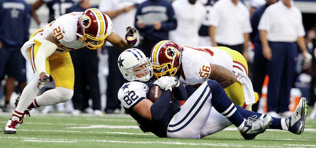 Dallas Cowboys' Jason Witten is tackled by Washington Redskins' Perry Riley as Redskins' Cedric Griffin moves in on the play during first half action Thursday Nov. 22, 2012 at Cowboys Stadium in Arlington, Tx. Photo: Edward A. Ornelas, Express-News / © 2012 San Antonio Express-News
