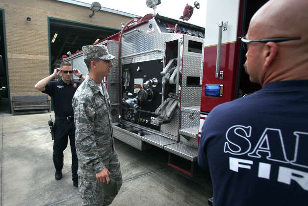 Lackland Airmen trainee Fulton, center, gets a ride on a fire truck to another fire station for Thanksgiving Dinner, Thursday, Nov. 22, 2012.  Eighteen San Antonio fire stations opened their doors for the trainees to share a home cooked dinner. Photo: Bob Owen, San Antonio Express-News / © 2012 San Antonio Express-News