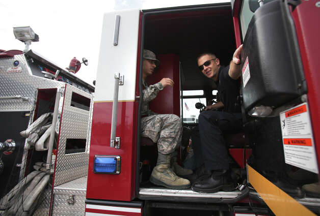 San Antonio Fire fighter G. Tilley, right, closes the door to a fire truck at Station 16, as Lackland Airman trainee Fulton, gets a ride to another station for Thanksgiving Dinner, Thursday, Nov. 22, 2012.  Eighteen San Antonio fire stations opened their doors for the trainees to share a home cooked dinner. Photo: Bob Owen, San Antonio Express-News / © 2012 San Antonio Express-News