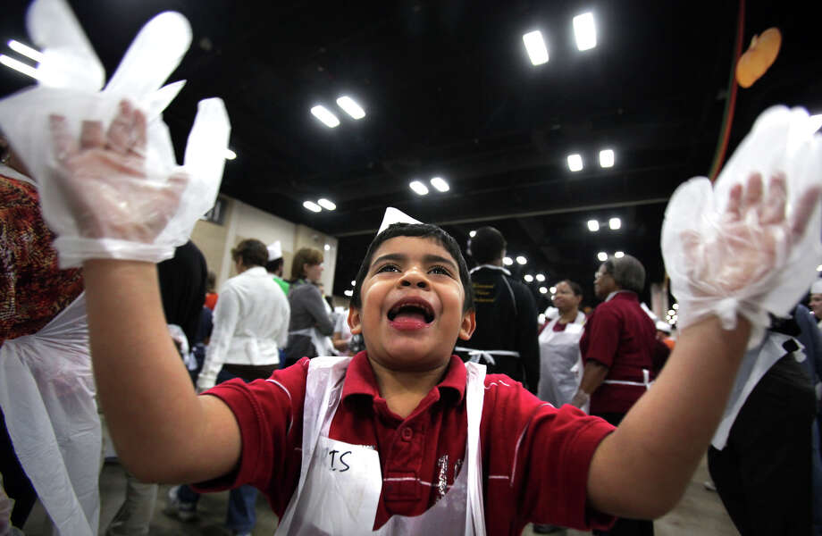 Five year old volunteer server Christopher Gonzales plays with his plastic glove covered hands as he waits for more turkey dinners to serve at the Raul Jimenez Thanksgiving Dinner at the Henry B. Gonzalez Convention Center, Thursday, Nov. 22, 2012. Photo: Bob Owen, San Antonio Express-News / © 2012 San Antonio Express-News
