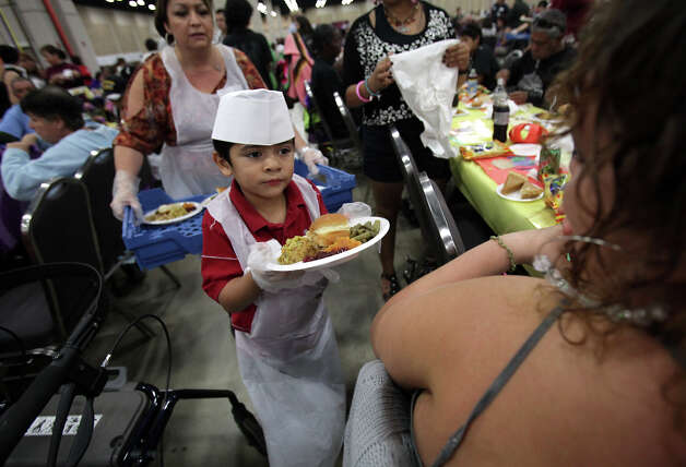 Christopher Gonzales, 5, serves a turkey dinner to Cecilia Hernandez, right, at the Raul Jimenez Thanksgiving Dinner at the Henry B. Gonzalez Convention Center, Thursday, Nov. 22, 2012. Photo: Bob Owen, San Antonio Express-News / © 2012 San Antonio Express-News
