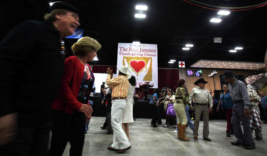 Holiday cheer can be seen on the dance floor at the Raul Jimenez Thanksgiving Dinner at the Henry B. Gonzalez Convention Center, Thursday, Nov. 22, 2012. Photo: Bob Owen, San Antonio Express-News / © 2012 San Antonio Express-News