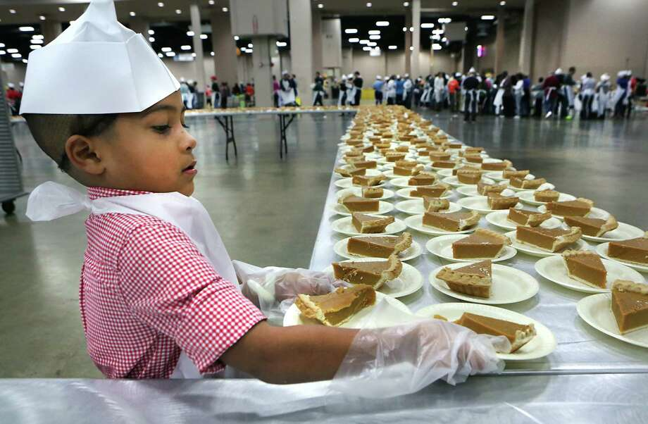 Volunteers serve up turkey dinners to seniors and people in need at the 33rd annual Raul Jimenez Thanksgiving Dinner at the Henry B. Gonzalez Convention Center, Thursday, Nov. 22, 2012. Photo: BOB OWEN, San Antonio Express-News / San Antonio Express-News