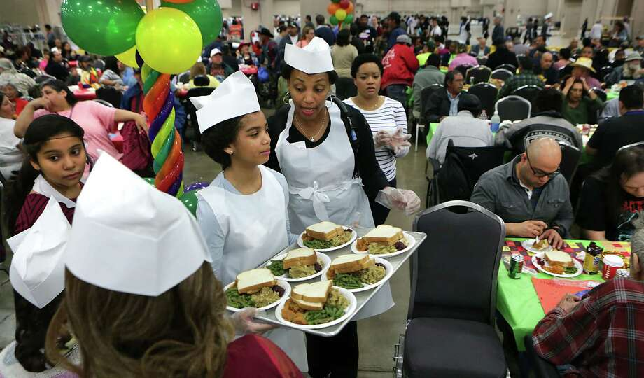 Adrian Gomez, right, transfers turkey to a full pan as he and Jerry McTyre, left, serve at the Raul Jimenez Thanksgiving Dinner at the Henry B. Gonzalez Convention Center, Thursday, Nov. 22, 2012. Photo: BOB OWEN, San Antonio Express-News / San Antonio Express-News