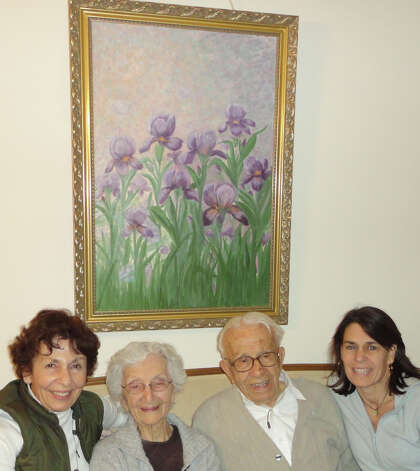Ann and John Betar are flanked by daughter Judy Metro, left, and granddaughter Heather Mitchell as they sit in Mitchell's living room under a painting of irises that was done by Ann Betar.  Fairfield CT 11/15/12 Photo: Meg Barone / Fairfield Citizen freelance