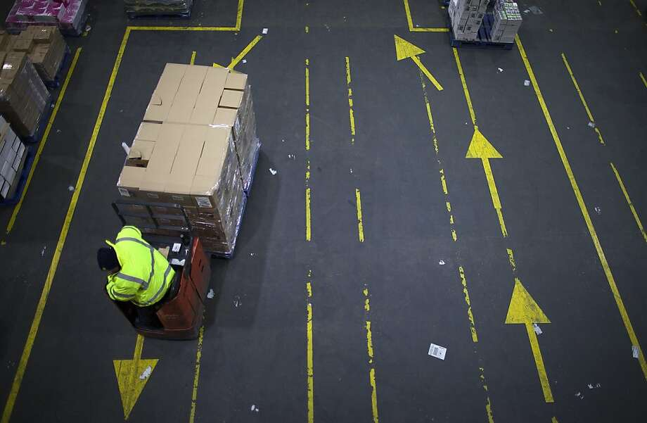 An employee maneuvers goods with a pallet truck inside WM Morrison Supermarkets Plc's distribution center in Wakefield, U.K., on Thursday, Nov. 22, 2012. Britain's economy will return to growth next year after stagnating in 2012, with expansion weighted in the second half, according to Bank of England projections published yesterday. Photographer: Simon Dawson/Bloomberg Photo: Simon Dawson, Bloomberg