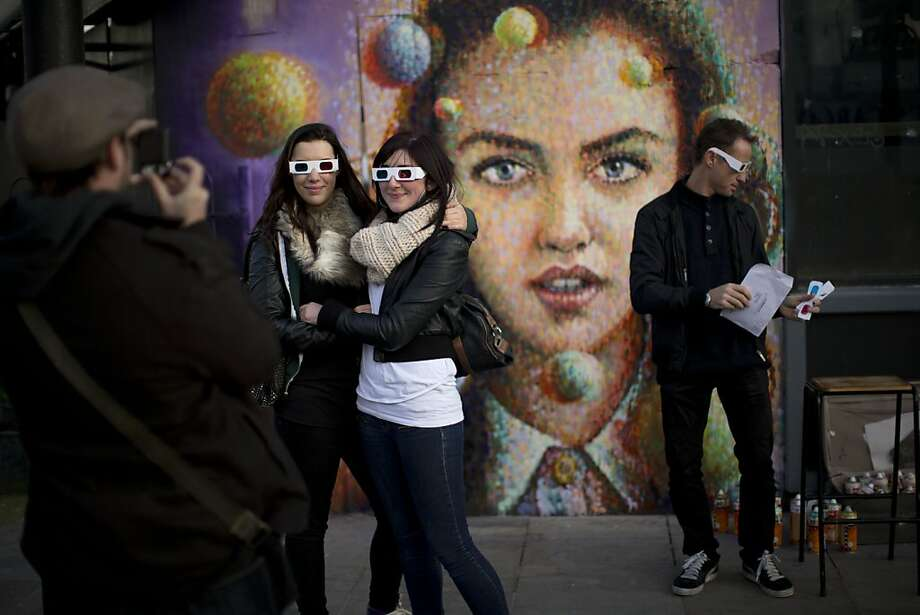 "People pose for a photograph in 3D glasses after viewing Australian artist James Cochran's, right, also known as Jimmy C, near finished spray paint 3D piece ""Girl with Spheres in 3D"" on the outside wall of a cafe in east London, Thursday, Nov. 22, 2012. The effects of the 3D painting can only be seen when the viewer looks through a pair of 3D glasses, which the cafe will keep a stock of to lend to people. (AP Photo/Matt Dunham) Photo: Matt Dunham, Associated Press"