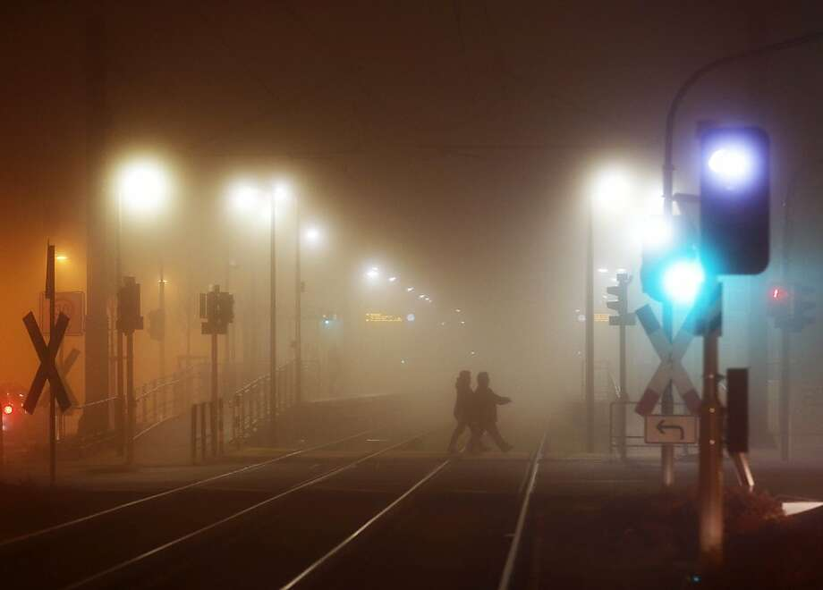 People cross tram rails in the suburbs on a foggy evening, Frankfurt, Germany, Thursday, Nov. 22, 2012. (AP Photo/Michael Probst) Photo: Michael Probst, Associated Press