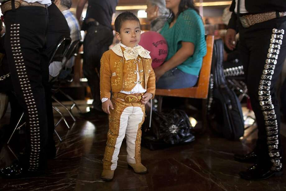 Cristopher Adair, 3, looks at the camera beside his father on the right, a Mariachi musician, during a mass in honor of Saint Cecilia, Mexico City, Thursday, Nov. 22, 2012.  Hundreds of people walked in procession to the Basilica of Guadalupe to honor Saint Cecilia, the patron saint of music. (AP Photo/Alexandre Meneghini) Photo: Alexandre Meneghini, Associated Press