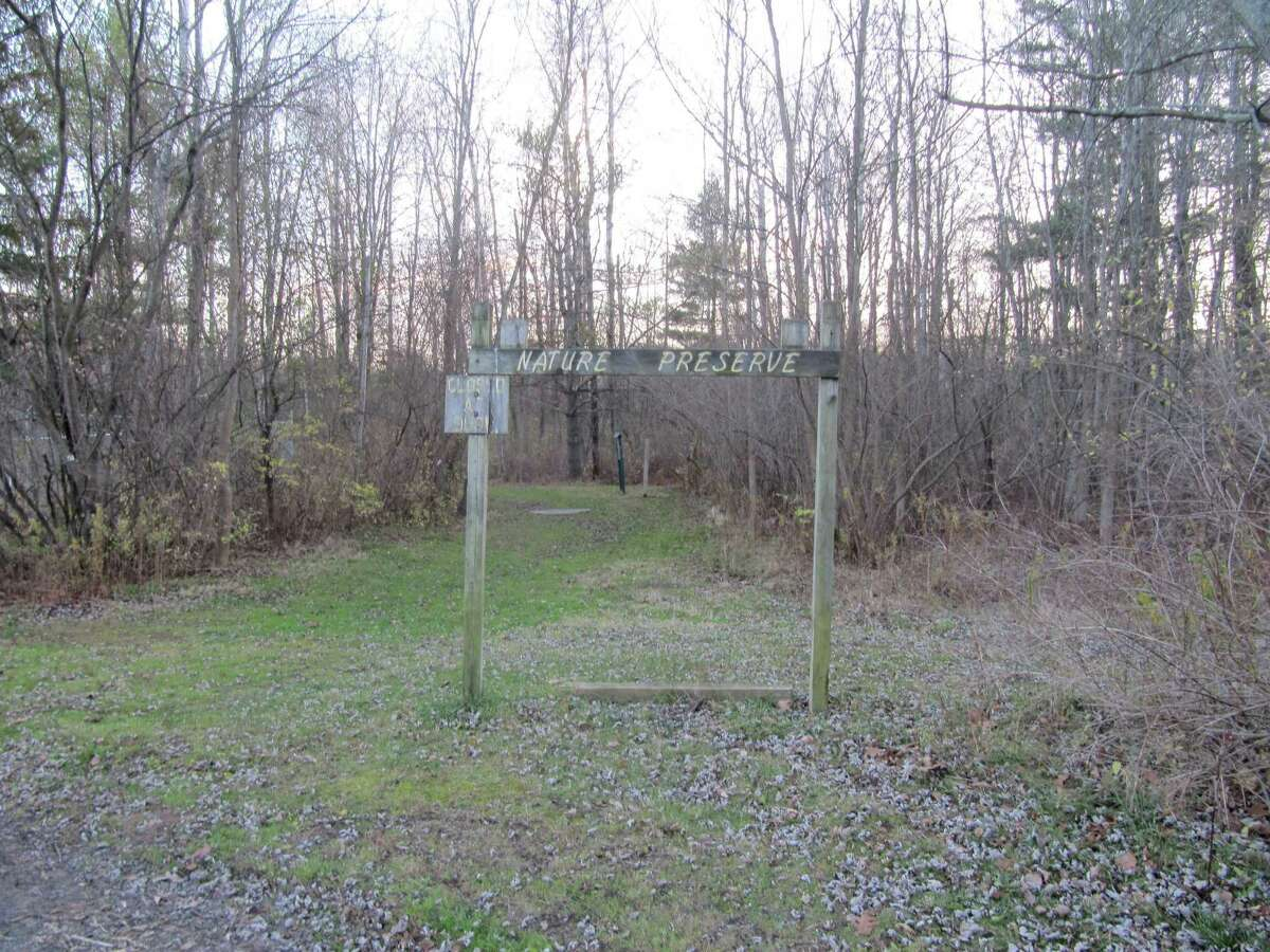 Photo by Gillian Scott. An old wooden sign marks the Whitmyer Drive trailhead leading into Mohawk River State Park in Niskayuna. The park land was formerly known as the Schenectady Museum Nature Preserve.