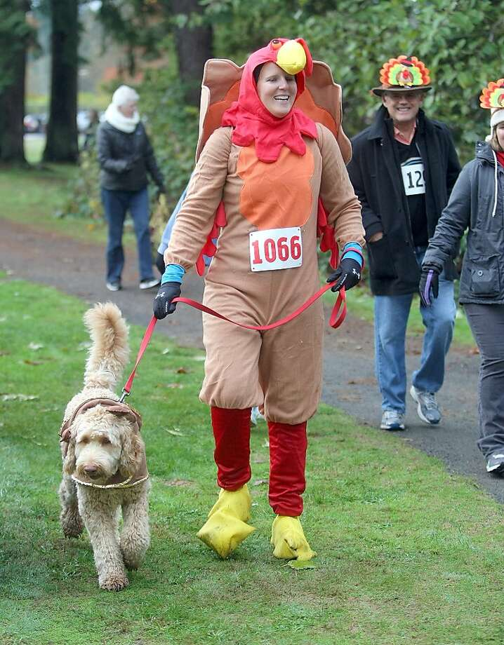 Palmer Fitzhugh of Bainbridge Island is dressed as a turkey as she walks in the one mile race at the 3rd annual Bainbridge Island Turkey Trot at Battle Point Park on Thursday, Nov. 22, 2012 in Bainbridge Island, Wash. The event was to benefit the Helpline House. She is with her dog Hurley who is dressed as a reindeer. (AP Photo/Kitsap Sun, Larry Steagall) Photo: Larry Steagall, Associated Press