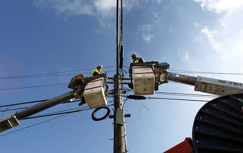 Linemen Bob Hauptvogel, right, and Rich Grinzo, right, work Thanksgiving Day, Thursday, Nov. 22, 2012. in Seaside Heights, N.J., to repair damage along the Jersey Shore from Superstorm Sandy. The American harvest holiday came as portions of the Northeast still were reeling from Sandy's havoc, and volunteers planned to serve thousands of turkey dinners to people it left homeless or struggling. (AP Photo/Mel Evans) Photo: Mel Evans, Associated Press