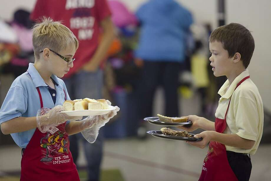 Volunteers Sebastian Lamb, 10, left, and Leroy Fischer serve food during the Salvation Army Thanksgiving Meal Thursday, Nov. 22, 2012 at the Salvation Army building at 810 E. 11th Street in Odessa, Texas. The Salvation Army served the meal to more than 50 people. (AP Photo/Odessa American, Albert Cesare) Photo: Albert Cesare, Associated Press
