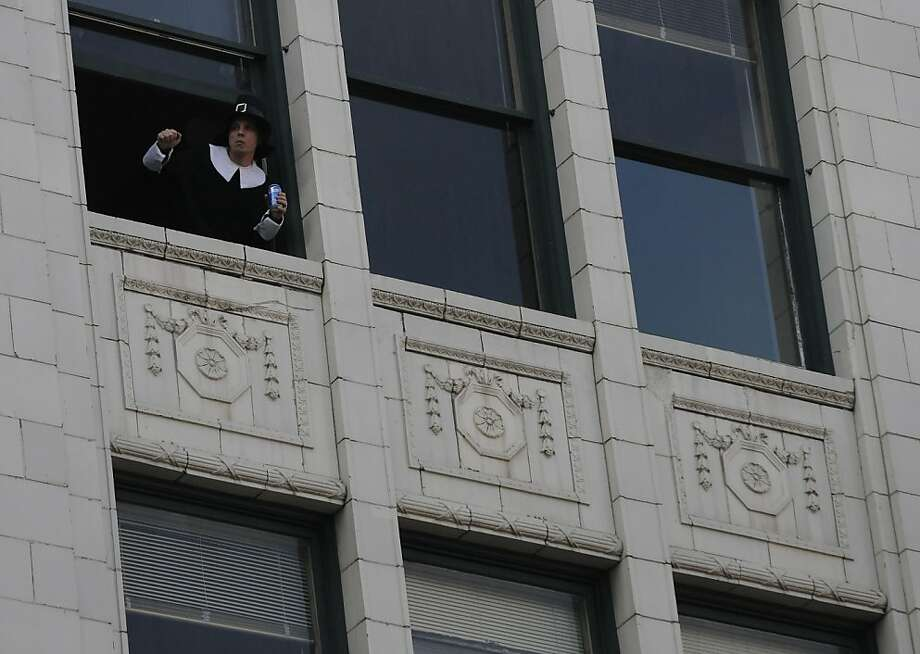 A spectator gets in the Thanksgiving spirit, or at least dress, watches the the 86th annual America's Thanksgiving Day Parade from the Lofts of Merchants Row on Woodward Avenue in Detroit on Thursday, Nov. 22, 2012. (AP Photo/The Detroit News, Elizabeth Conley) Photo: Elizabeth Conley, Associated Press