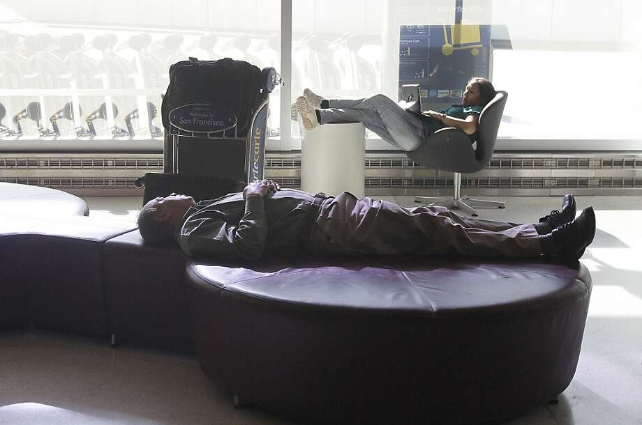 Travelers rest in a waiting area in the domestic terminal of San Francisco International Airport in San Francisco, Thursday, Nov. 22, 2012. (AP Photo/Jeff Chiu) Photo: Jeff Chiu, Associated Press