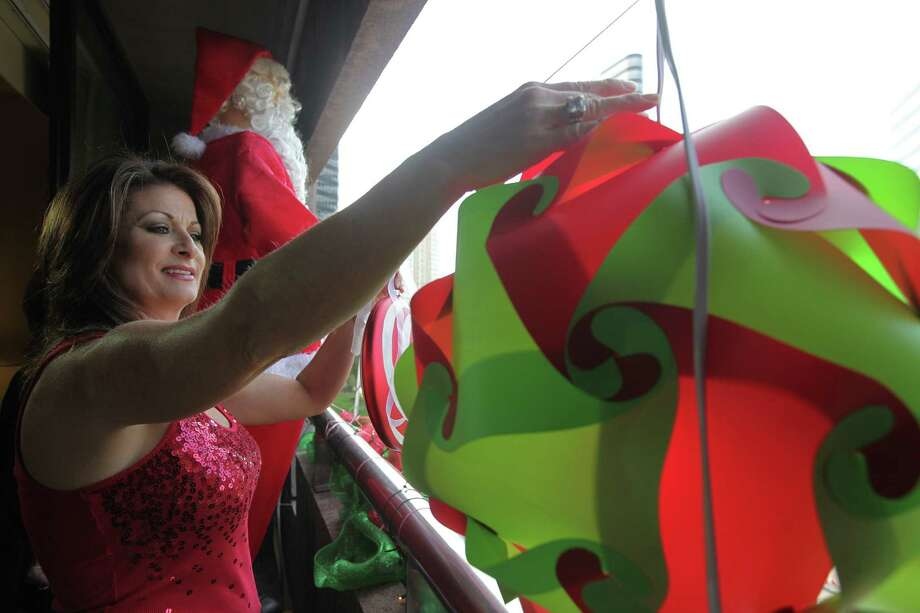 Diana Denman helps decorate a balcony overlooking The 27th Annual Uptown Houston Holiday Lighting Celebration on Thursday, Nov. 22, 2012, in Houston. Photo: Mayra Beltran, Houston Chronicle / © 2012 Houston Chronicle