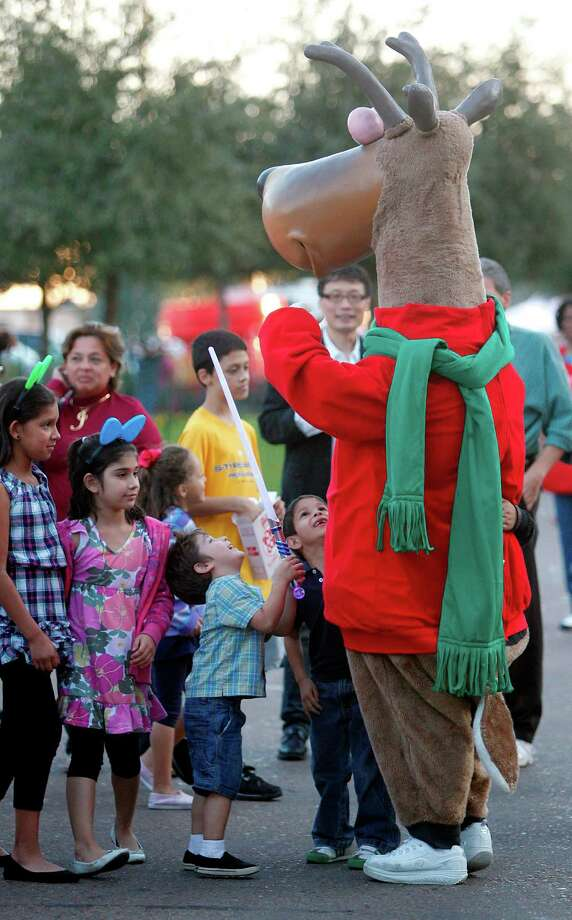 Children gather around the reindeer for a photo during The 27th Annual Uptown Houston Holiday Lighting Celebration on Thursday, Nov. 22, 2012, in Houston. Photo: Mayra Beltran, Houston Chronicle / © 2012 Houston Chronicle