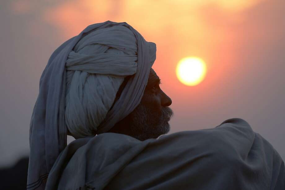 A camel trader sits in a field at sunset in the camel fair grounds in the outskirts of the small town of Pushkar on November 21, 2012. Thousands of livestock traders from the region come to the traditional camel fair where livestock but mainly camels are traded. This annual five-day camel and livestock fair is one of the world's largest camel fairs.  AFP PHOTO/Roberto SchmidtROBERTO SCHMIDT/AFP/Getty Images Photo: Roberto Schmidt, AFP/Getty Images