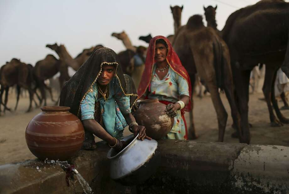 Indian women pause as they collect water for their camp at the annual Pushkar Fair in Pushkar, Rajasthan, India, Thursday, Nov. 22, 2012. The annual camel and livestock fair attracts thousands of livestock dealers who bring thousands of camels, horses, and cattle. (AP Photo/Kevin Frayer) Photo: Kevin Frayer, Associated Press