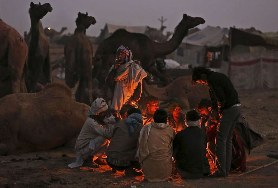 Indian camel herders warm themselves on a fire at the annual Pushkar Fair in Pushkar, Rajasthan, India, Thursday, Nov. 22, 2012. The annual camel and livestock fair attracts thousands of livestock dealers who bring thousands of camels, horses, and cattle. (AP Photo/Kevin Frayer) Photo: Kevin Frayer, Associated Press
