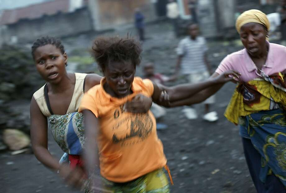 Congolese women run after Congolese soldiers and rebel fighters battled for hours over the eastern Congolese town of Sake , 27 kilometers (17 miles) west of Goma, Thursday, Nov. 22, 2012. The woman in orange only identified as Mamou, said she lost her husband to a fatal wound to the head from incoming mortar round. Thousands fled the M23 controlled town as the militants seeking to overthrow the government vowed to push forward despite mounting international pressure. (AP Photo/Jerome Delay) Photo: Jerome Delay, Associated Press