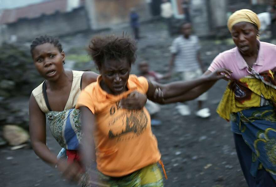 Congolese women run after Congolese soldiers and rebel fighters battled for hours over the eastern C