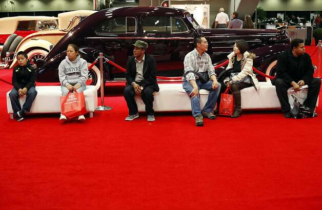 Spectators take a break in the Academy of Art University classic car collection exhibit at opening day of the 55th San Francisco International Auto Show in San Francisco, Calif., Thursday, November 22, 2012. Photo: Sarah Rice, Special To The Chronicle