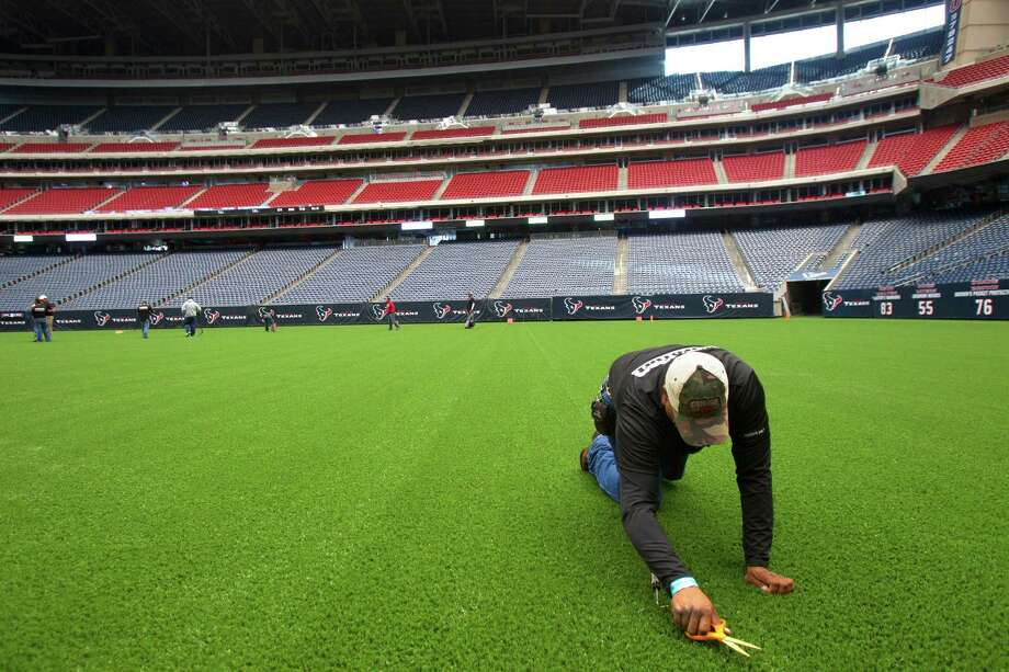 Fransisco Lares cuts taller strands of synthetic grass from Reliant Stadium's new surface in advance of high school playoff action. Photo: Cody Duty, Staff / © 2012 Houston Chronicle