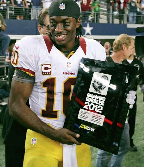 Washington Redskins' Robert Griffin III holds the 2012 Galloping Gobbler award after the game with t