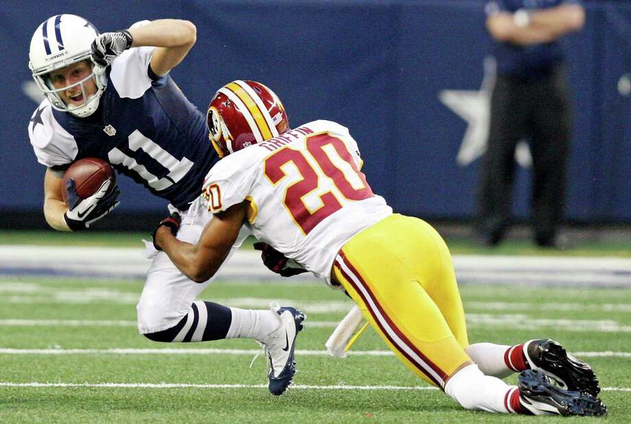 Dallas Cowboys' Cole Beasley is tackled by Washington Redskins' Cedric Griffin during first half action Thursday Nov. 22, 2012 at Cowboys Stadium in Arlington, Tx. Photo: Edward A. Ornelas, Express-News / © 2012 San Antonio Express-News
