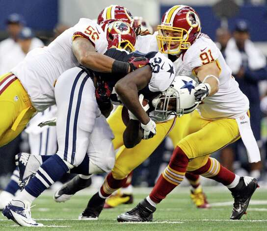 Dallas Cowboys' Felix Jones is tackled by Washington Redskins' Perry Riley (left) and Washington Redskins' Ryan Kerrigan during first half action Thursday Nov. 22, 2012 at Cowboys Stadium in Arlington, Tx. Photo: Edward A. Ornelas, Express-News / © 2012 San Antonio Express-News