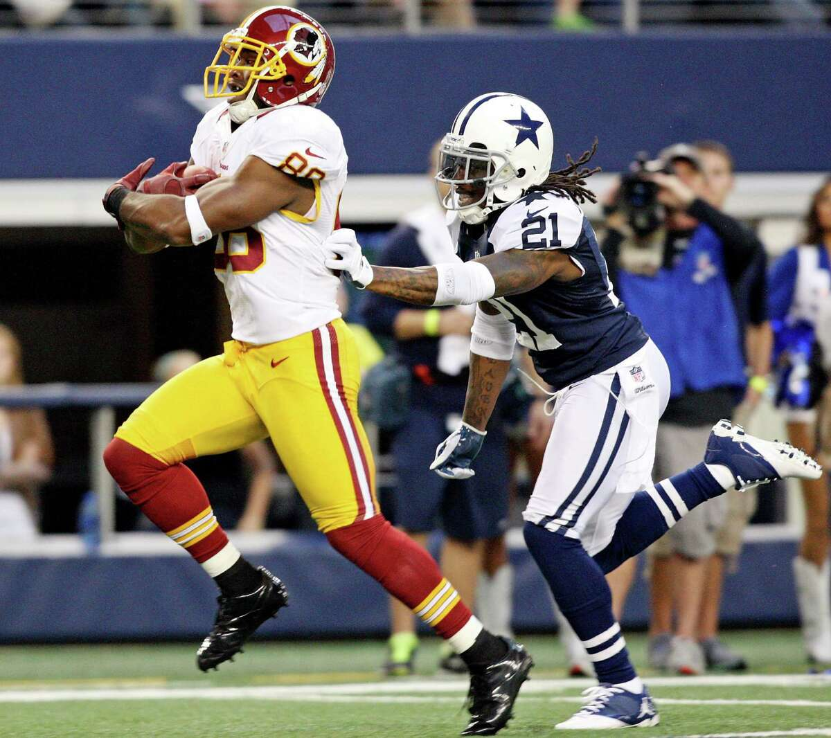 Washington Redskins' Pierre Gar�on heads to the end zone for a touchdown ahead of Dallas Cowboys' Mike Jenkins during first half action Thursday Nov. 22, 2012 at Cowboys Stadium in Arlington, Tx.
