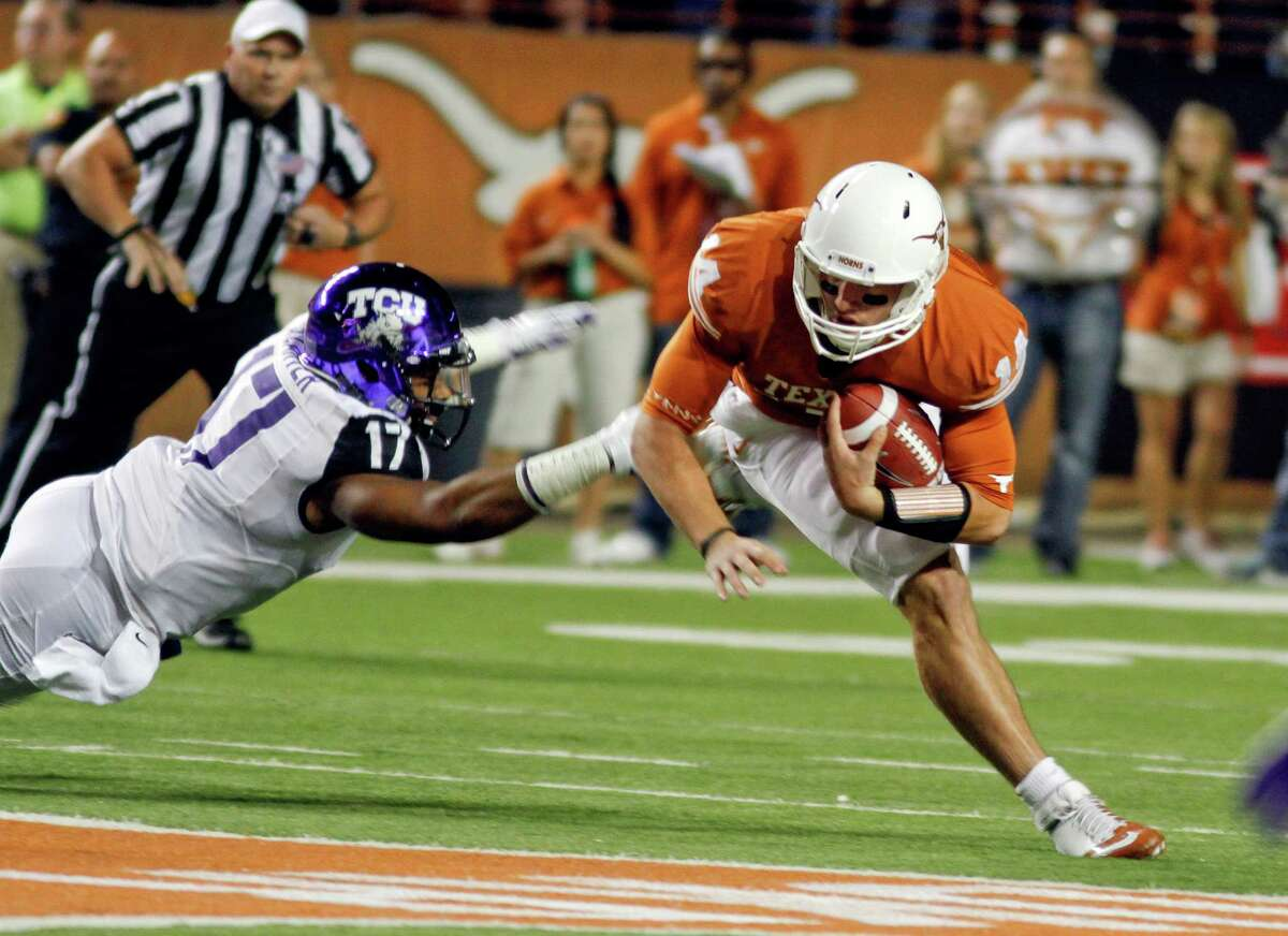 Texas quarterback David Ash, right, is brought down by TCU's Sam Carter (17) during the first half of an NCAA college football game on Thursday, Nov. 22, 2012, in Austin, Texas. (AP Photo/Jack Plunkett)