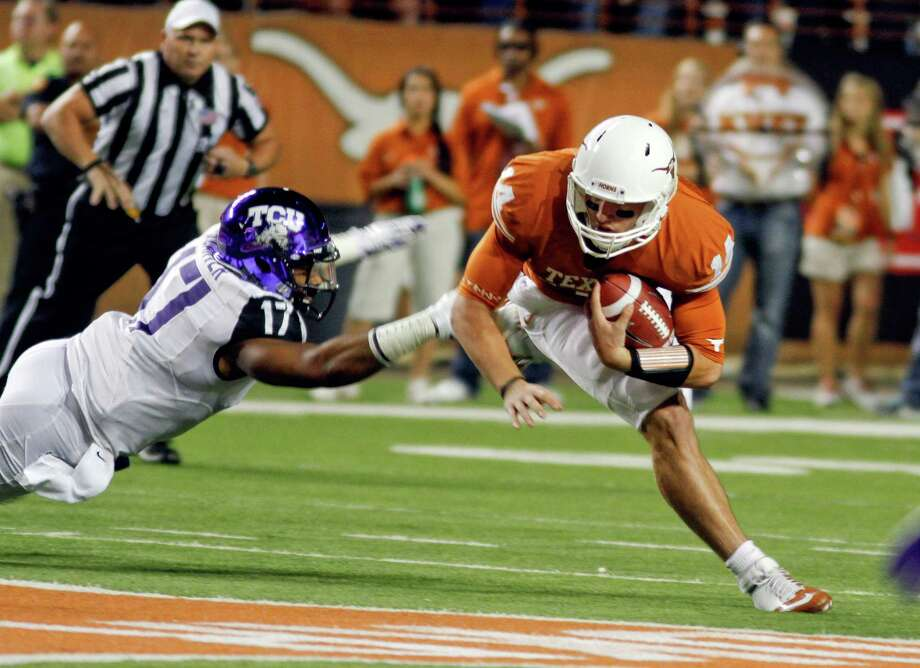 Texas quarterback David Ash, right, is brought down by TCU's Sam Carter (17) during the first half of an NCAA college football game on Thursday, Nov. 22, 2012, in Austin, Texas. (AP Photo/Jack Plunkett) Photo: Jack Plunkett, Associated Press / FR59553 AP