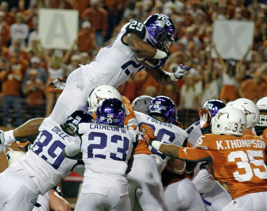 TCU tailback Matthew Tucker (29) jumps over the Texas defense to score during the first half of an NCAA college football game on Thursday, Nov. 22, 2012, in Austin, Texas. (AP Photo/Jack Plunkett) Photo: Jack Plunkett, Associated Press / FR59553 AP