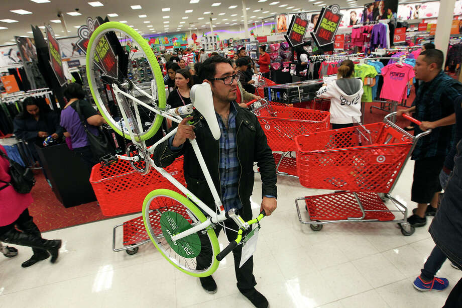 Juan Moreno hoists a bicycle on his shoulders to avoid running into people as he joins hundreds of shoppers at Super Target at Wonderland of the Americas on Thursday, Nov. 22, 2012. Target opened at 9 p.m. on Thanksgiving Day for shoppers looking for sales ahead of Black Friday. Photo: Kin Man Hui, San Antonio Express-News / ©2012 San Antonio Express-News