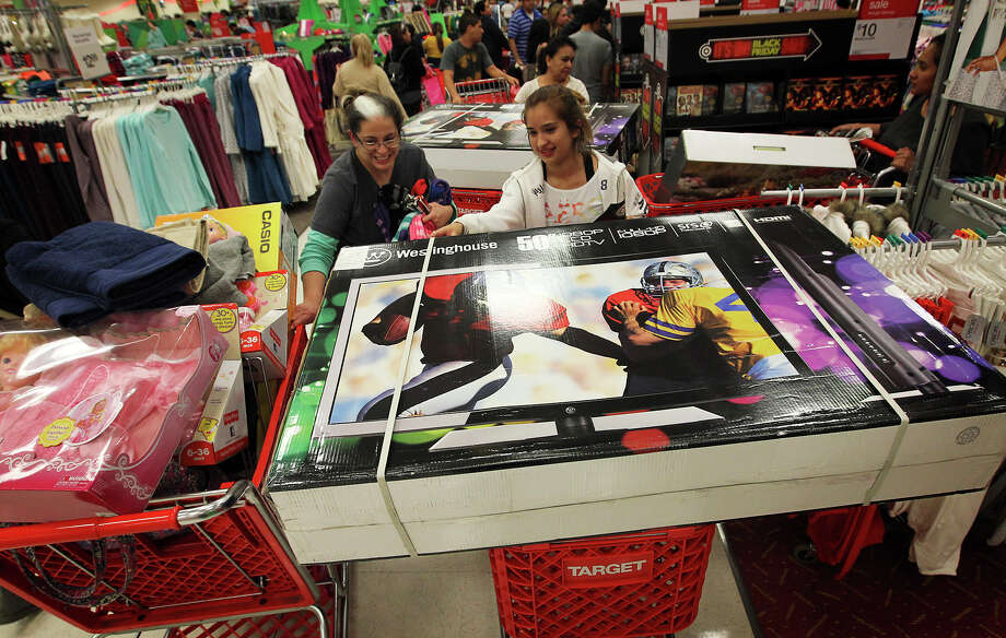 Ashley Martinez (right) has a challenge navigating her shopping cart with a 50-inch television as she joins hundreds of shoppers at Super Target at Wonderland of the Americas on Thursday, Nov. 22, 2012. Target opened at 9 p.m. on Thanksgiving Day for shoppers looking for sales ahead of Black Friday. Photo: Kin Man Hui, San Antonio Express-News / ©2012 San Antonio Express-News