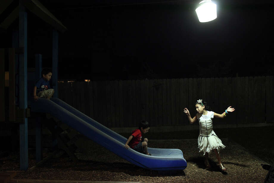 Jillian Diaz, 8, right, plays on the church's playground with her brothers, Santos Diaz, 3, center, and Peter Diaz, 4, left, after a service at Calvary Church on Tuesday, Nov. 20, 2012. Photo: Lisa Krantz, San Antonio Express-News / © 2012 San Antonio Express-News