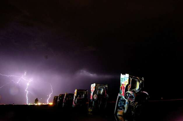 Texas Panhandle residents may have heard the clap of thunder early Wednesday morning, Aug. 13, 2008, as several rainstorms rolled across the high plains outside Amarillo. Lightning illuminated the night sky and the partially buried cars at the Cadillac Ranch. Photo: Michael Schumacher, AP / Amarillo Globe-News
