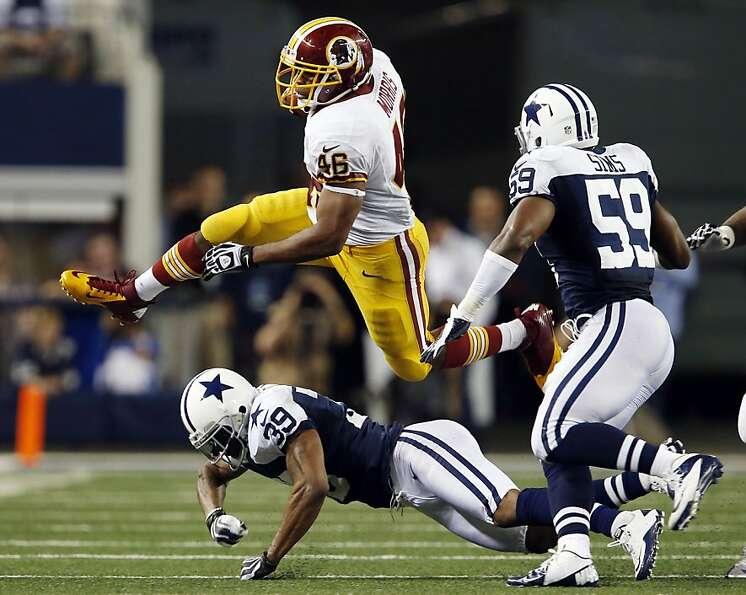 Washington Redskins cornerback Josh Wilson (26) jumps over Dallas Cowboys cornerback Brandon Carr (3