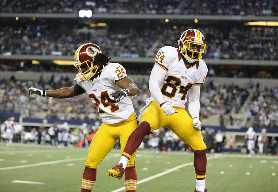 Washington Redskins strong safety DeJon Gomes (24) and tight end Niles Paul (84) celebrate a touchdown reception by Paul in the second half of an NFL football game against the Dallas Cowboys Thursday, Nov. 22, 2012, in Arlington, Texas. The Redskins won 38-31. (AP Photo/Matt Strasen) Photo: Matt Strasen, Associated Press