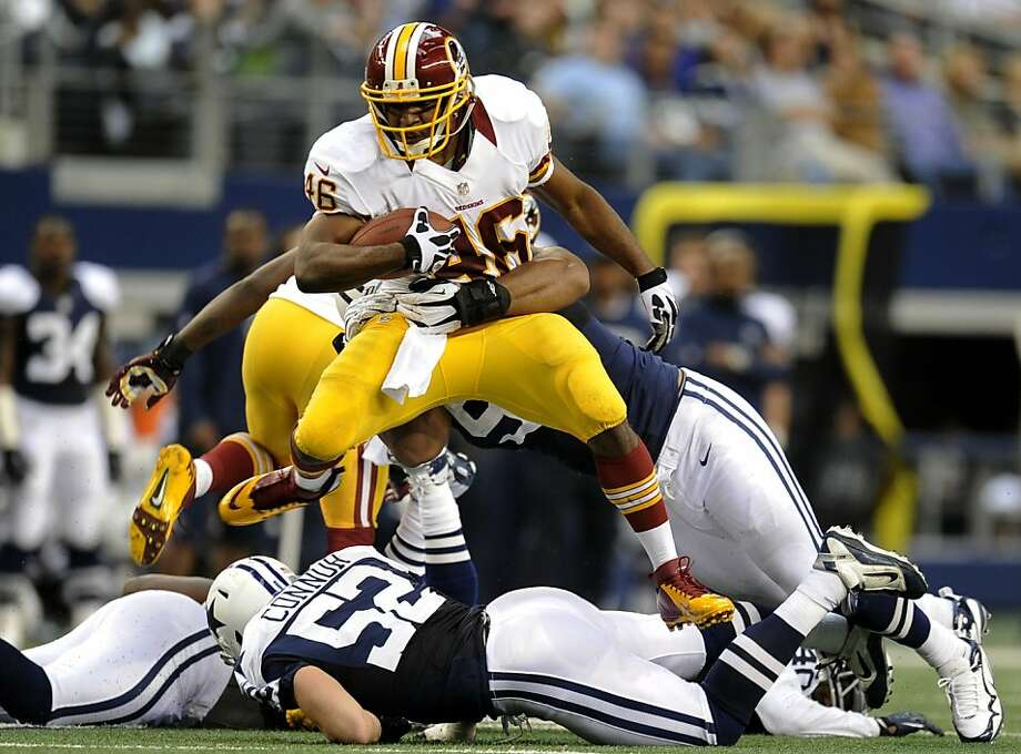 Washington Redskins running back Alfred Morris (46) leaps over Dallas Cowboys' Dan Connor (52) as he tries to escape a tackle by Jason Hatcher, rear, in the first half of an NFL football game, Thursday, Nov. 22, 2012, in Arlington, Texas. (AP Photo/Matt Strasen) Photo: Matt Strasen, Associated Press