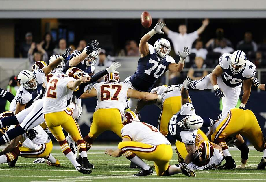 Washington Redskins kicker Kai Forbath (2) makes a field goal as Dallas Cowboys' Tyrone Crawford (70) and Ben Bass (79) attempt to block it late in the second half of an NFL football game, Thursday, Nov. 22, 2012, in Arlington, Texas. The Redskins won 38-31. (AP Photo/Matt Strasen) Photo: Matt Strasen, Associated Press