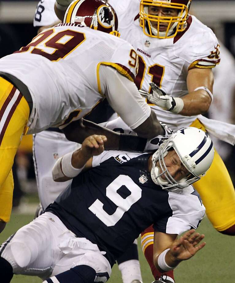 Dallas Cowboys quarterback Tony Romo (9) is knocked to the ground by Washington Redskins' Jarvis Jenkins (99) with help from Ryan Kerrigan, rear, in the second half of an NFL football game, Thursday, Nov. 22, 2012, in Arlington, Texas. (AP Photo/Tim Sharp) Photo: Tim Sharp, Associated Press