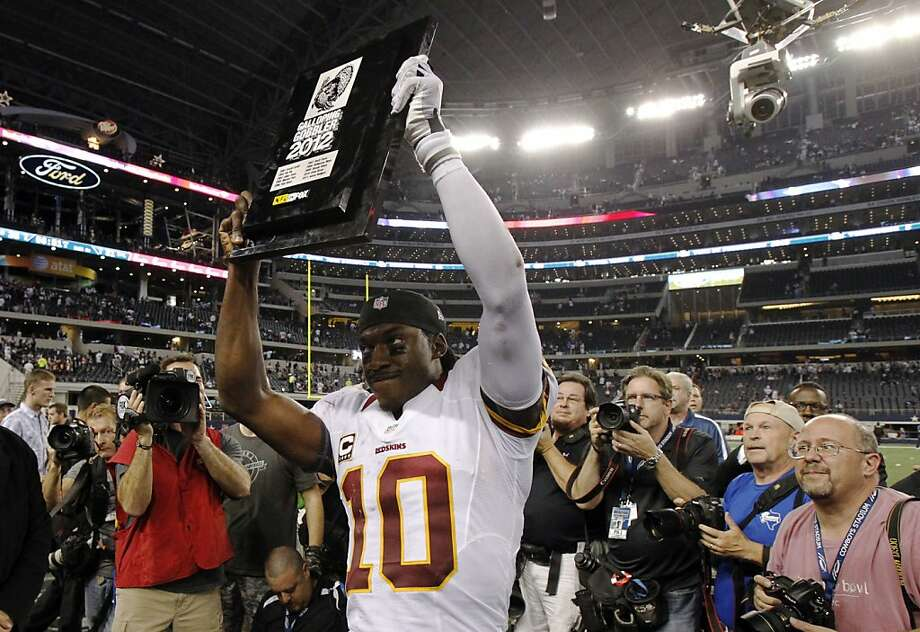Washington Redskins quarterback Robert Griffin III (10) holds up his Galloping Gobbler  2012 award following their 38-31 win over the Dallas Cowboys in an NFL football game Thursday, Nov. 22, 2012 in Arlington, Texas. (AP Photo/Tim Sharp) Photo: Tim Sharp, Associated Press